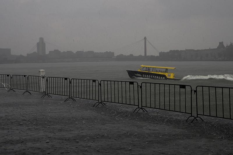 De kade van de Maas in de buurt van de Erasmusbrug tijdens een wolkbreuk.